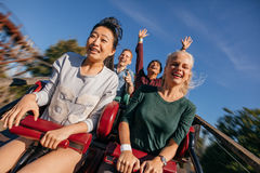 Group of friends on a thrilling roller coaster ride. Young people on a thrilling roller coaster ride. Group of friends having fun at amusement park royalty free stock photo