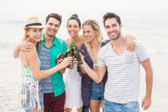Group of friends toasting beer bottles on the beach. Group of happy friends toasting beer bottles on the beach royalty free stock photos