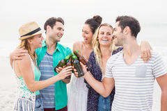 Group of friends toasting beer bottles on the beach. Group of happy friends toasting beer bottles on the beach royalty free stock photography
