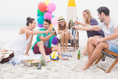 Group of friends toasting beer bottles on the beach. On a sunny day Royalty Free Stock Photography