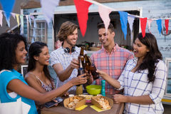 Group of friends toasting beer bottles. In office cafeteria Royalty Free Stock Images