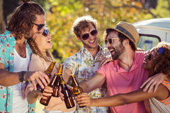Group of friends toasting beer bottles. In park Stock Photography