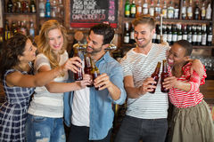Group of friends toasting beer bottles at pub. Group of cheerful friends toasting beer bottles at pub stock photo