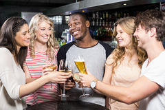 Group of friends toasting with beer and wine. In a night club Stock Photos
