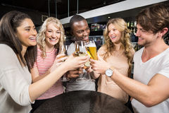 Group of friends toasting with beer and wine. In a night club Royalty Free Stock Photography