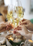 Group of friends toasting with champagne while having Christmas Stock Image