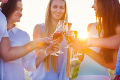 Group of friends toasting champagne sparkling wine at the beach. Group of friends toasting champagne sparkling wine at a relax party celebration gathering at the royalty free stock photo