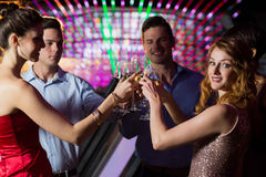 Group of friends toasting glasses of champagne. Group of smiling friends toasting glasses of champagne in bar royalty free stock image