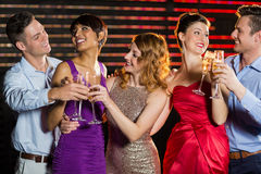 Group of friends toasting glasses of champagne. Group of smiling friends toasting glasses of champagne in bar stock photography