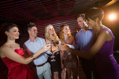 Group of friends toasting glasses of champagne. Group of smiling friends toasting glasses of champagne in bar stock images