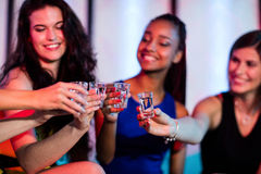 Group of friends toasting tequila shot glasses. In bar Royalty Free Stock Image