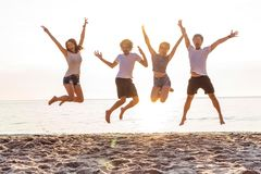 Group of friends together on the beach having fun. Happy young people jumping on the beach. Group of friends enjoying royalty free stock photo