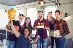 A group of friends with a torus with candles at a birthday party. In a room Stock Photography
