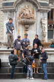 Group of friends tourists under a monument in Italy Royalty Free Stock Image