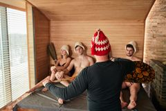 Group of friends in a traditional russian steam-room with bath attendant stock photography
