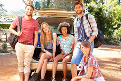 Group Of Friends On Trip Sitting In Trunk Of Car Stock Image