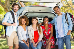 Group of friends on trip sitting in trunk of car Stock Photography