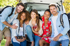 Group of friends on trip sitting in trunk of car Royalty Free Stock Photo