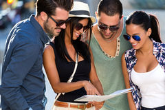 Group of friends use their map in the street. Royalty Free Stock Images