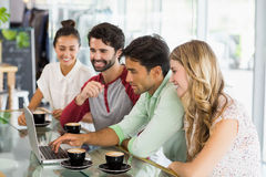 Group of friends using laptop while having cup of coffee Royalty Free Stock Image