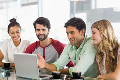 Group of friends using laptop while having cup of coffee Royalty Free Stock Images