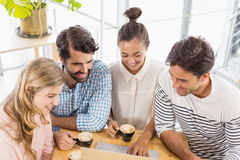 Group of friends using laptop while having cup of coffee Royalty Free Stock Photography