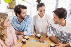 Group of friends using laptop while having cup of coffee Royalty Free Stock Photos