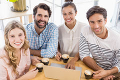 Group of friends using laptop while having cup of coffee Stock Photos