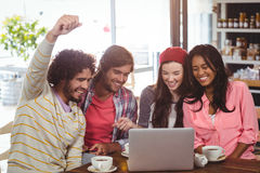 Group of friends using laptop while having cup of coffee Stock Image