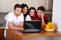Group of friends using laptop in kitchen Stock Image