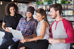 Group friends using laptop in restaurant. Group of smiling friends using laptop in restaurant royalty free stock photos