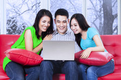 Group of friends using laptop on sofa Royalty Free Stock Photos