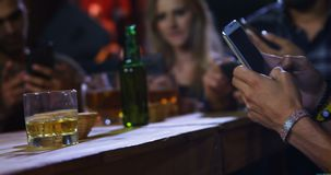 Group of friends using mobile phone. In bar stock video footage