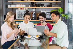 Group of friends using mobile phone, digital tablet and laptop Royalty Free Stock Photography