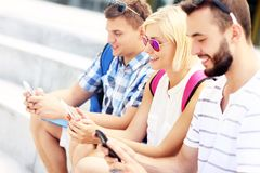 Group of friends using smartphones in the campus Stock Image