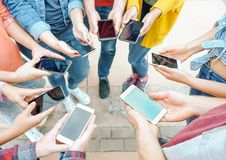 Group of friends using their smart mobile phones - Millennial young people addicted to new technology trends royalty free stock photography