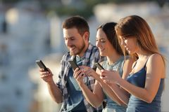 Group of friends using their smart phones. Group of three friends using their smart phones in a town outskirts stock images
