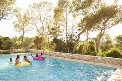 Group Of Friends On Vacation Relaxing In Outdoor Pool Royalty Free Stock Photo