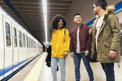 Group of friends waiting the train in the platform of subway station. stock images