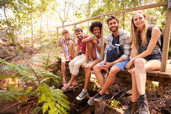Group Of Friends On Walk Sitting On Wooden Bridge In Forest Royalty Free Stock Image