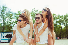 Group of friends walking along the beach, with men giving piggyback ride to girlfriends. Stock Photos