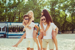 Group of friends walking along the beach, with men giving piggyback ride to girlfriends. Royalty Free Stock Photo