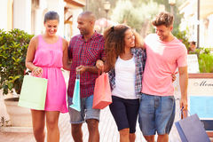 Group Of Friends Walking Along Street With Shopping Bags Stock Photo