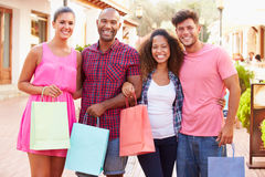 Group Of Friends Walking Along Street With Shopping Bags Stock Image