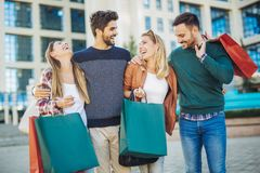 Friends walking along street with shopping bags Stock Images