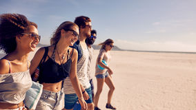 Group of  friends walking on the beach. Group of five friends walking on the beach. Two young men and three young women on a summer beach vacation Royalty Free Stock Photo