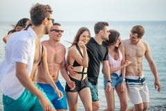 Group of Friends Walking at Beach, having fun, womans piggyback on mans, funny vacation. Multiracial Group of Friends Walking at Beach, having fun, womans royalty free stock photo