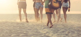 Group of friends walking on the beach at sunset. Royalty Free Stock Photo