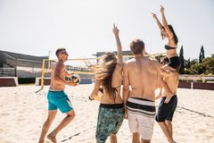Group of friends walking on the beach volleyball court at sunny morning. royalty free stock photography