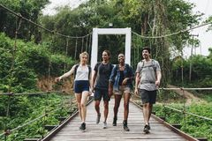 Group of friends walking on the bridge in a tropical countryside adventure and journey concept Royalty Free Stock Photo